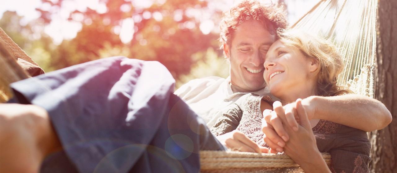 Lachendes Paar liegt in Hängematte.